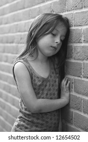 Shot of a depressed young girl against a brick wall