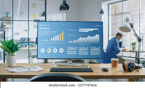 Shot of a Desktop Computer in the Creative Modern Office. Monitor Screen Shows Company Growth Data with Graphs, Charts, Software UI. In the Background Young Professional Using Smartphone.