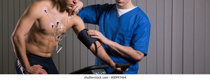Shot of a doctor checking electrodes on a sportsman's body