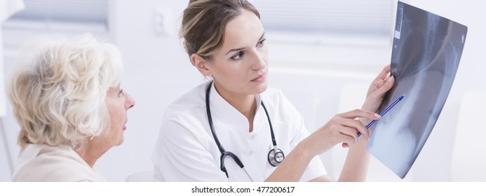 Shot of a doctor showing her patient an x-rey