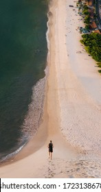 Shot from drone. A young man in mask and black dress run barefoot along a curving  white sand beach with sea waves. Social distancing, sports and covid19. Photo in the style of the film Inception. - Shutterstock ID 1723138678