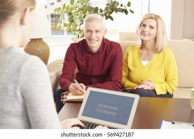 Shot of an elderly couple sitting at home and consulting with their financial advisor about banking online.