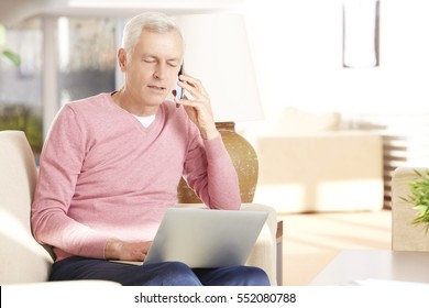Shot of an elderly man sitting with his mobile phone and laptop and banking online.