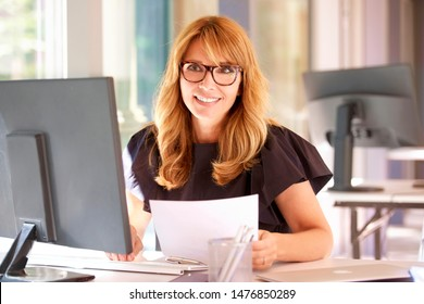 Shot of elegant mature businesswoman sitting in front of computer and doing some paperwork while working in the office.