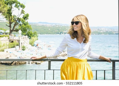 Shot of an elegant middle aged woman wearing sunglasses while standing at balcony by the sea.