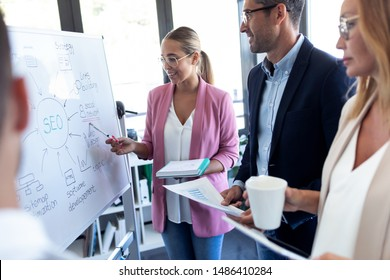 Shot of elegant young businesswoman pointing at white blackboard and explain a project to her colleagues on coworking place.