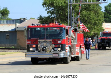 A shot of an Ellsworth Co Fire Truck in a Parade in Wilson Kansas USA. With the US Flag,blue sky,green tree's, and people in the parade. That's on 7-27-2019.