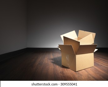 Shot of empty boxes on the floor of an empty room during a house move. The boxes have been lit with a spot so the rest of the room goes dark and the designer can use light type over darker areas