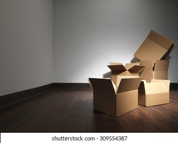 Shot of empty boxes in an empty room as if the occupants of a house were moving. This is similar to another submission but has darker walls in case the designer wants to add light text.