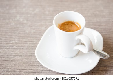Shot of espresso in the  white cup close up.