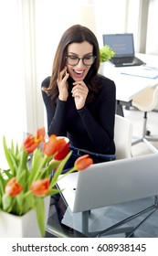 Shot of an excited young businesswoman talking with her client and working on laptop in the office.