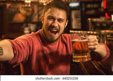Shot of an excited young man screaming happily taking a selfie with a glass of beer relaxing at the local pub people emotions expressing shouting amazement enjoyment happiness lifestyle concept