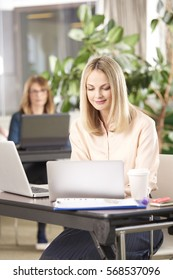 Shot of an executive financial businesswoman using laptops while her coworkers working in the background.