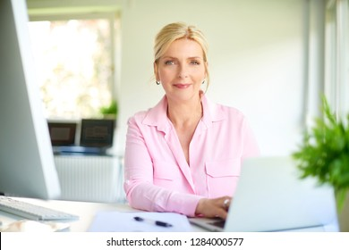 Shot of an executive senior businesswoman sitting at office desk and using her laptop while working on new project.