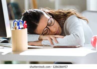 Shot of exhausted young business woman who has fallen asleep while working in the office.