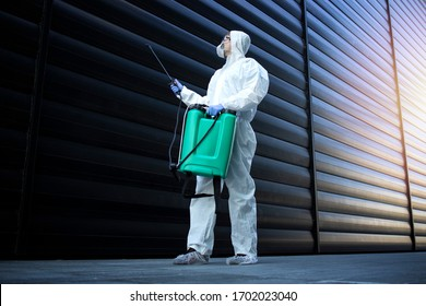 Shot of exterminator person in white chemical protection suit doing disinfection and pest control and spraying poison to kill insects and rodents. Successful pest control and extermination.