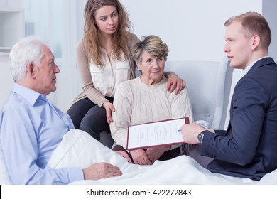 Shot of a family listening to a young man holding a last will form