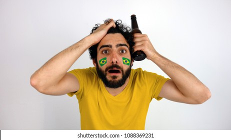 Shot of fan is disappointed with the team of his country. Man with the flag of Brazil makeup on his face and yellow t-shirt.