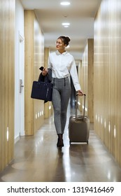 Shot of fashionable young businesswoman walking with suitcase looking for her room in the corridor of the hotel.