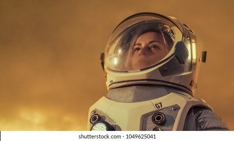 Shot of Female Astronaut in the Space Suit Looking Around Alien Planet. Red and Orange Planet Similar to Mars. Advanced Technologies, Space Travel, Colonization Concept.