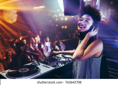 Shot of a female DJ playing music at a nightcub