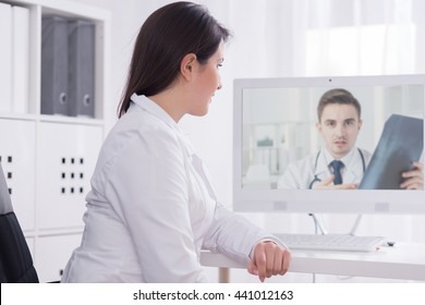 Shot of a female doctor in a doctor's room talking on-line with her colleague who is holding a radiograph