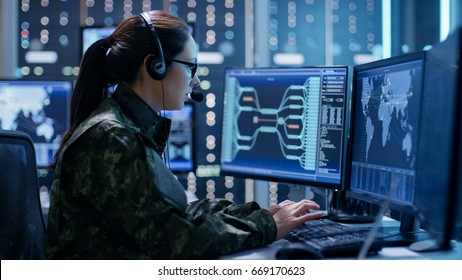 Shot of Female Government Agent Tracking Fugitive with Her Computer in Big Monitoring Room Full of Computers with Animated Screens.
