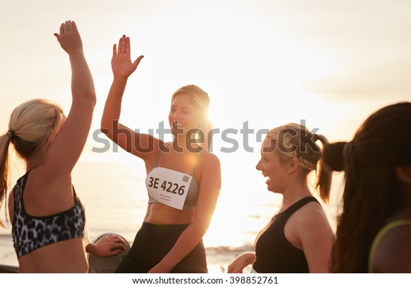 Shot of female runners high fiving each other after a race. Group of athletes giving each other high five after winning competition.
