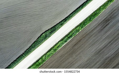 Shot of the field from drone. Farmers field. Road between fields. Background or texture - Shutterstock ID 1554822734