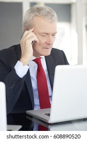 Shot of a financial managing director sitting in front of laptop and analyzing financial data.