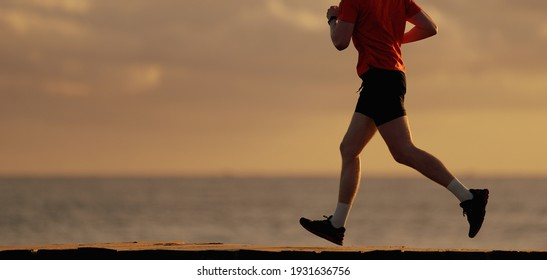 Shot of fit man running along the ocean shore in morning. Healthy male jogging on the beach