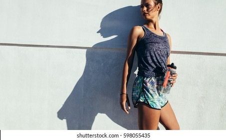 Shot of fit runner standing against a wall outdoors. Sporty woman relaxing after running exercise.