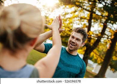 Shot of fit young man giving high five to woman. Fitness couple in park giving high five.