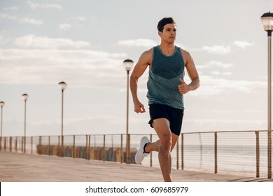 Shot of fit young man running on seaside promenade. Male runner exercising outdoors.