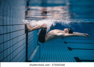 Shot of fit young man turning over underwater. Pro male swimmer in action inside swimming pool.