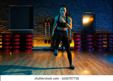 Shot of fit young woman doing jump aerobic exercises at gym. Aerobic and fitness exercises.