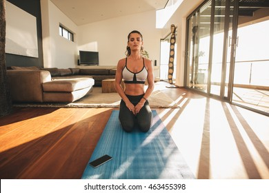 Shot of fit young woman practicing yoga indoors. Fitness female model sitting Vajrasana yoga pose and meditating on exercise mat at home.