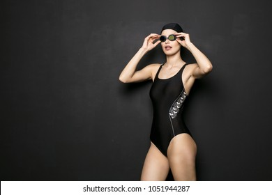 shot of fit young woman in swimming costume looking to camera on black background. Female swimmer looking focused before her workout
