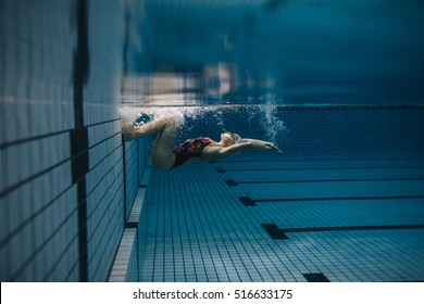 Shot of fit young woman turning over underwater. Female swimmer in action inside swimming pool.