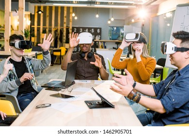 Shot of five young coworkers testing virtual reality glasses in office. Business people wearing VR goggles