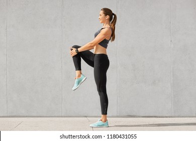 Shot of flexible young woman warms up before jogging on stadium, wears sportsclothes, shows her stomach and abs, poses against grey concrete wall. People, sport, fitness and flexibility concept