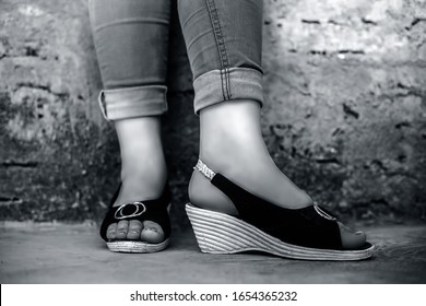 Shot of foot of elegant young teen girl wearing blue denim jeans and peep-toe sandals posing crossed legs against brick wall background in black and white color.