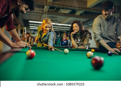 Shot of four friends playing billiards