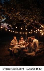 Shot of four handsome friends having dinner in the backyard