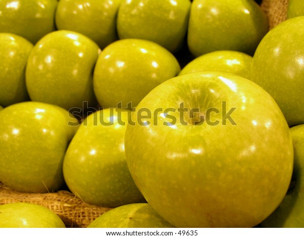 Shot of fresh green apples in a supermarket - focus mainly on the apple in front.