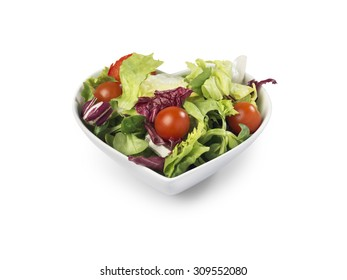 shot of fresh salad in a heart shaped bowl implying healthy living isolated on white with a clipping path and copy space for the designer.