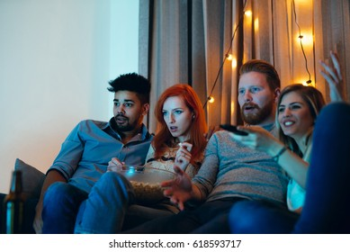 Shot of friends hanging out in the apartment and watching a game.