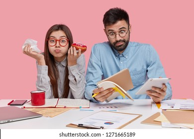 Shot of funny brunette woman eats delicious doughnut, has full mouth while her partner realizes shocking news, stares at notepad, holds touchpad, compares information, isolated over pink background