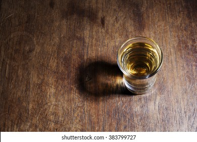 A shot glass of Brazilian gold cachaca isolated on rustic wooden background