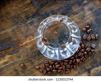 Shot glass of Sambuca, an italian alcoholic drink,  with coffee beans on old weathered wooden table
